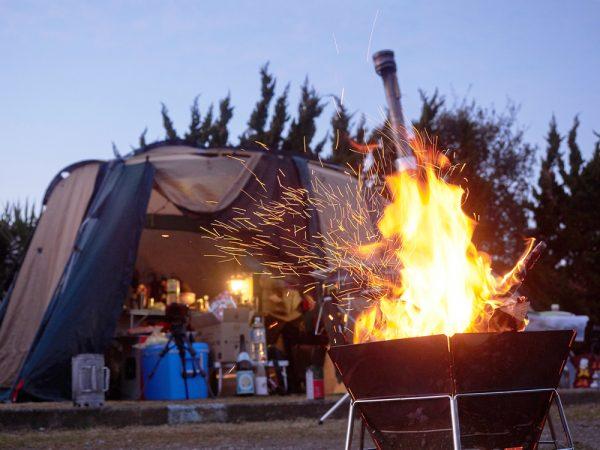 風の強い火の焚き火とテント